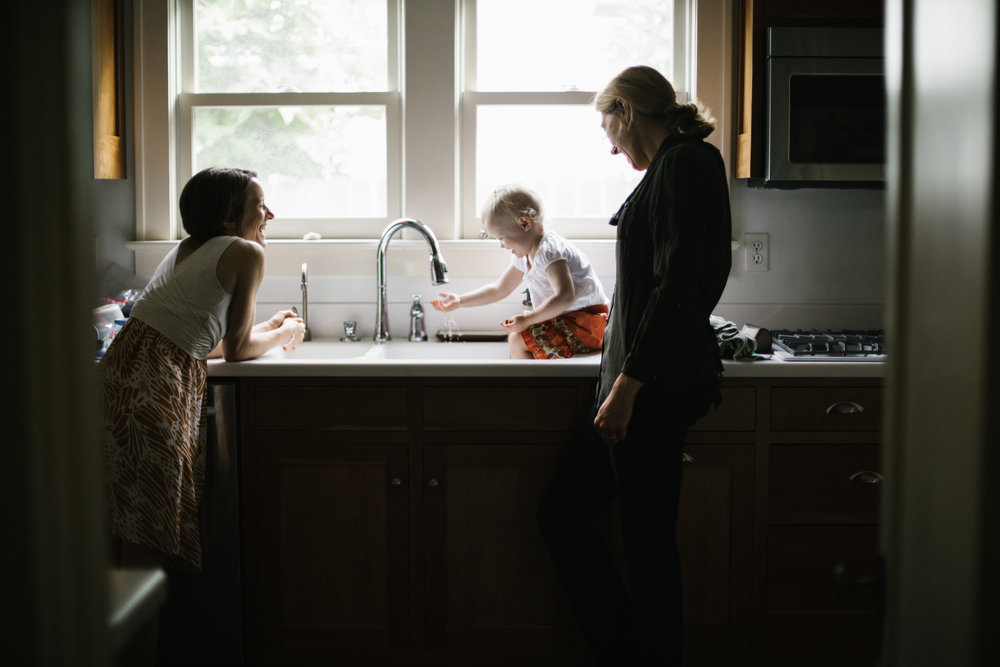 family playing in kitchen sink