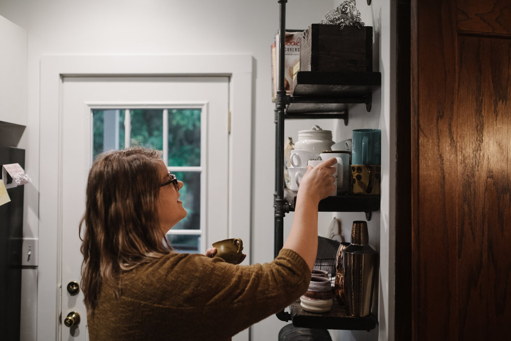 Woman grabbing mug off shelf