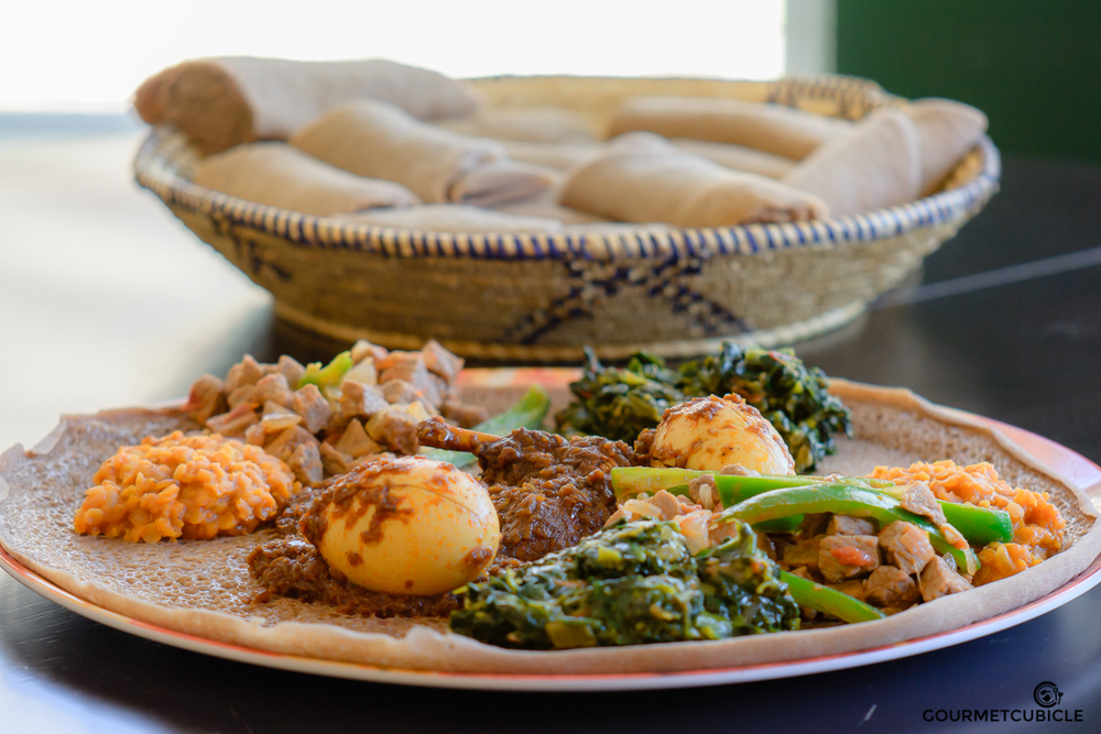 Misir Wot (lentils stew), Doro Wot (chicken stew), Gomen (Ethiopian collard green) and Beef Tibs served on injera bread.