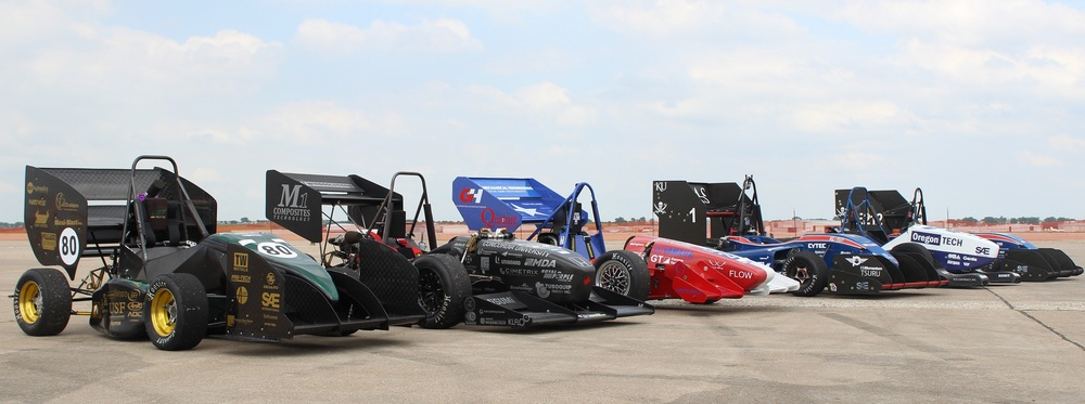 The 2015 competition car lined up with various other universities. (left to right: University of South Florida, Concordia University, Texas A&M University, Kentucky University, Oregon Tech, Kentucky University)