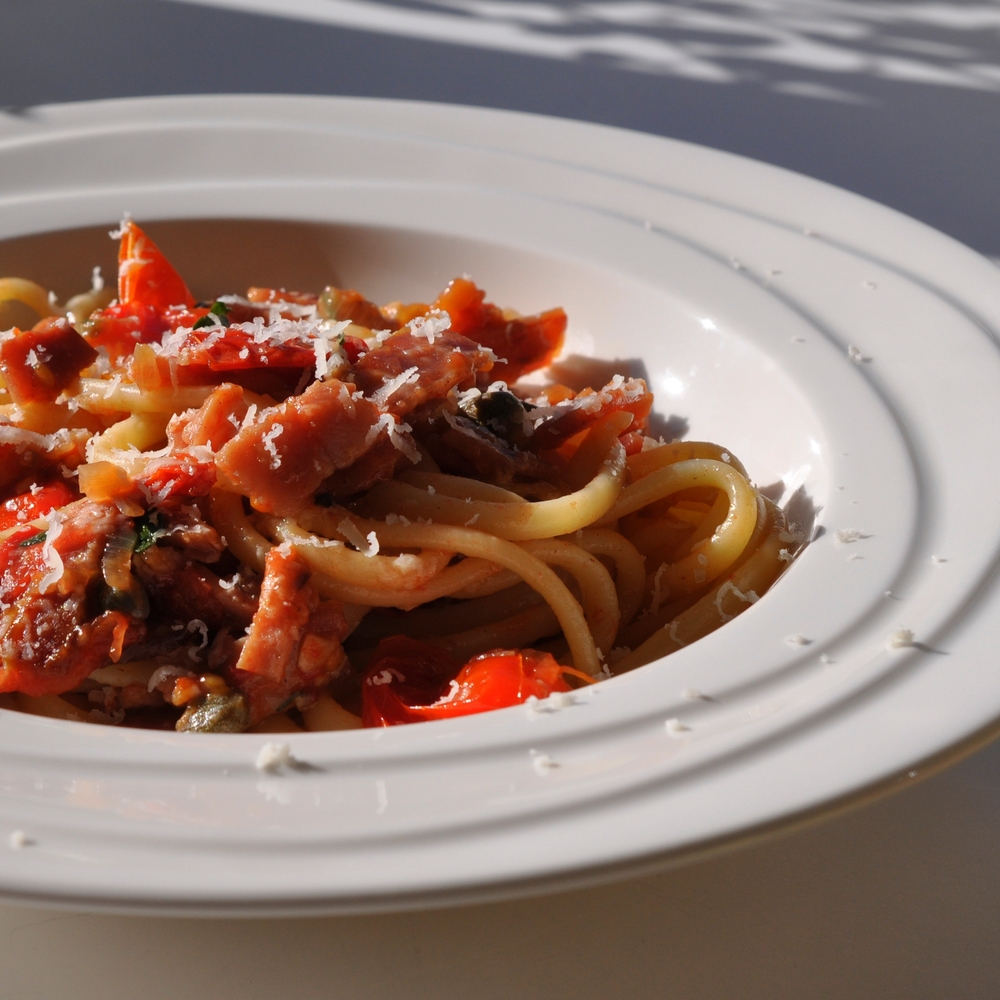 Spaghetti with tomatoes bacon capers and mint