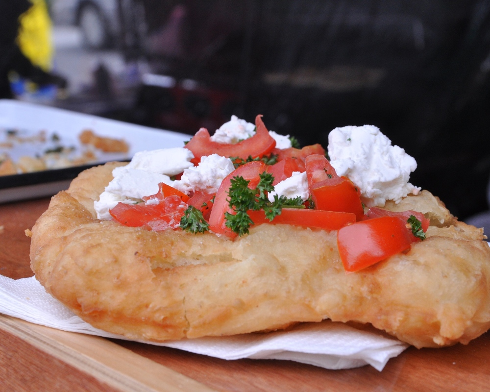 Hungarian bread puffs topped with feta and tomatoes