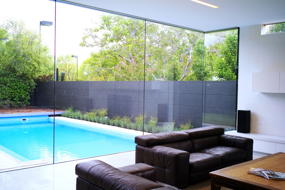 Glass walls bring light into the living room and showcase the pool beyond