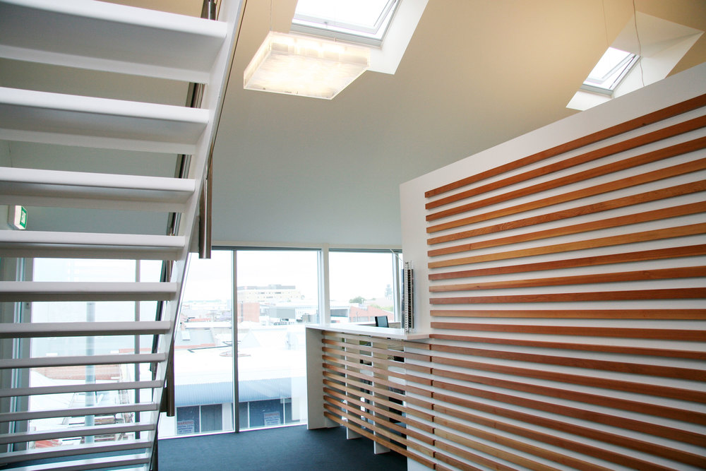 Skylights and Western-city views bounce off a timber feature wall to welcome visitors to the office