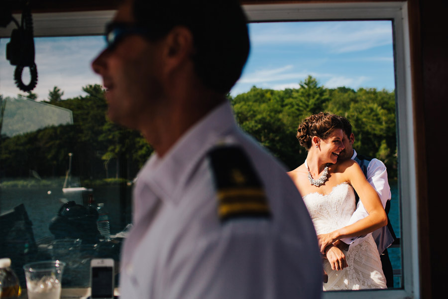 bride and groom holding each other on a boat on lake winnipesaukee wedding