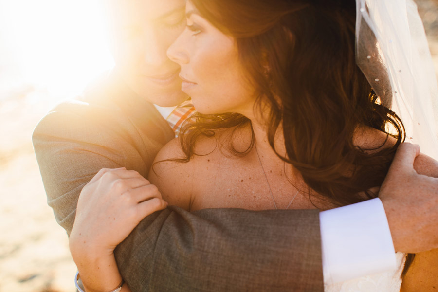 stunning new england bride with her groom on the beach during sunset
