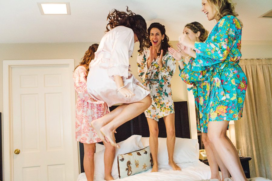 beautiful new england bride jumping on the bed with bridesmaids
