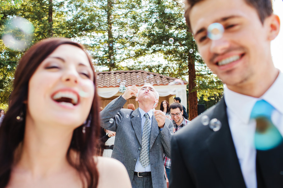 bride and groom leaving ceremony with bubbles in california
