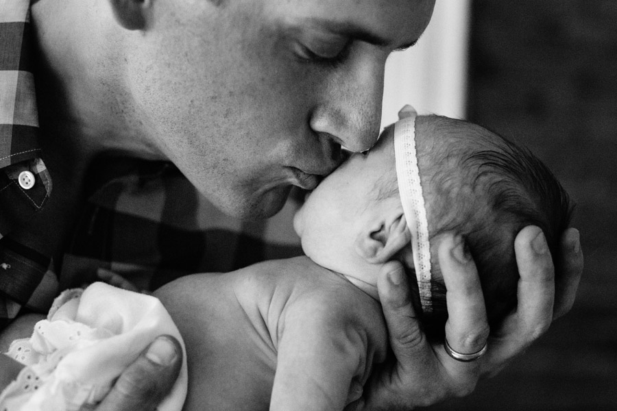 father kissing 3 week old daughter boston family photographer