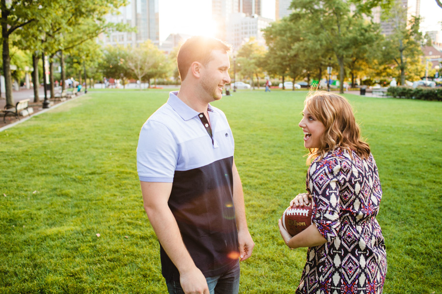 stunning boston engagement session at christopher columbus park couple playing football