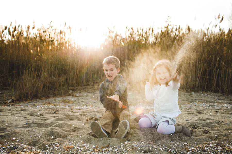 Lifestyle beautiful family photography on a beach in rhode island - boston photographer mikhail glabets throwing sand