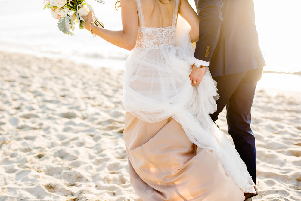bride and groom walking on the beach at ocean edge resort
