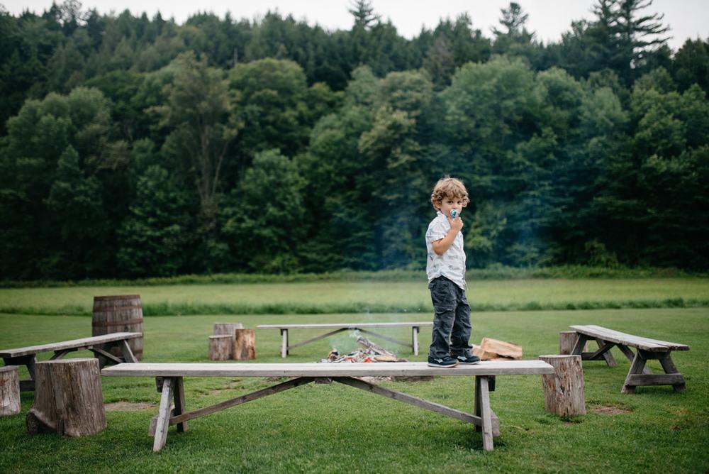 cute kid at a wedding rehearsal dinner at Lareau Farm Inn in Vermont
