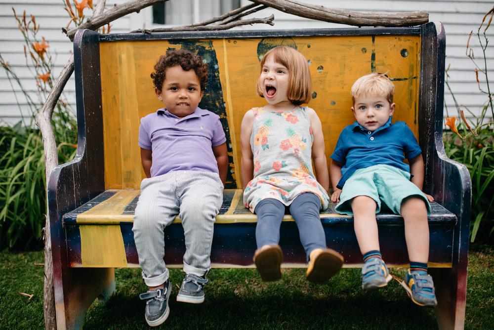 cute kids on a bench having fun at a wedding rehearsal dinner at Lareau Farm Inn in Vermont