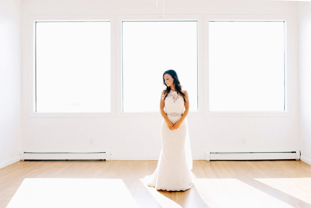 beautiful bride standing in window at belle mer wedding venue