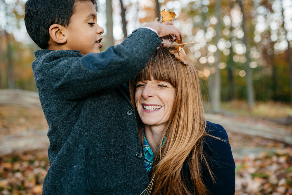 kid putting leaves on moms head during fall in new england family lifestyle photos and location inspiration