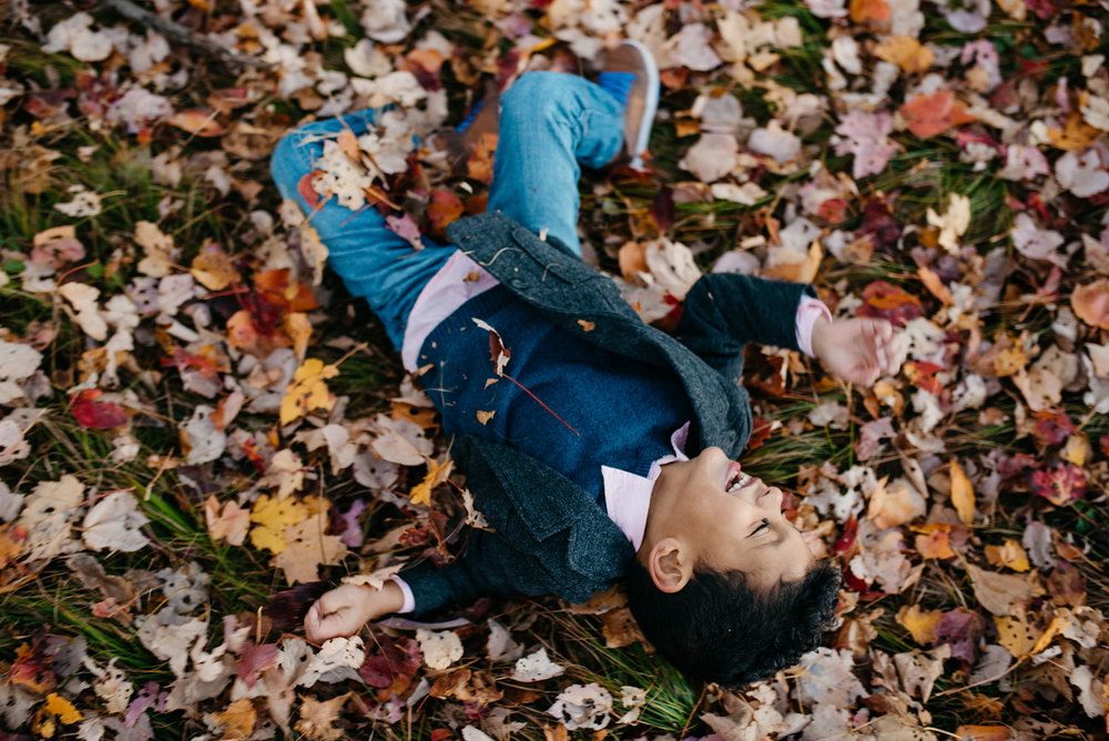 cute kid rolling in the leaves new england photographer and lifestyle photos