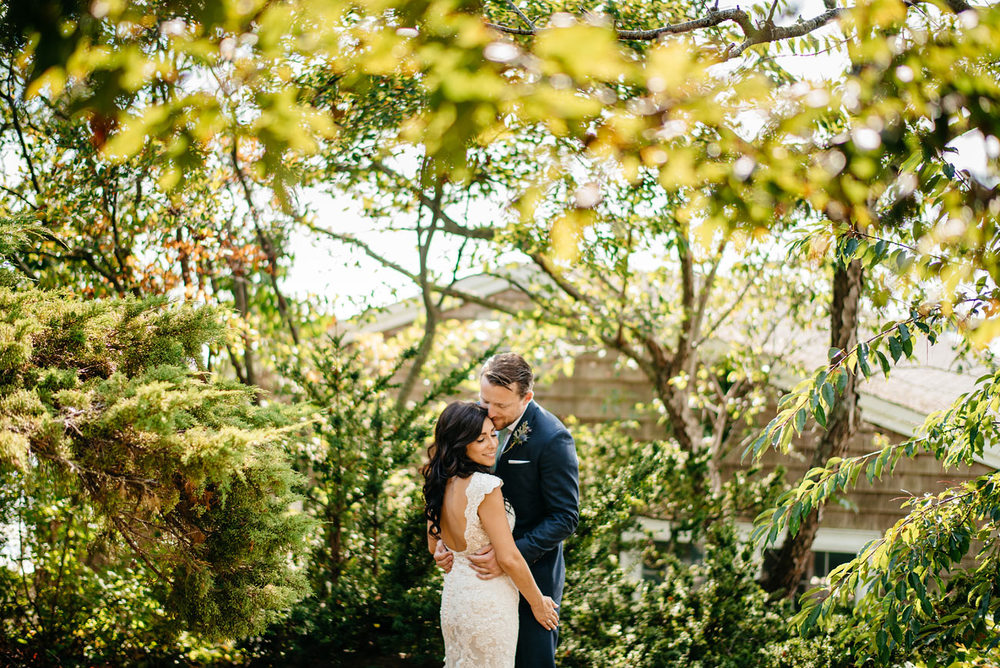 creative and beautiful eastern point yacht club in Gloucestor, MA creative portraits bride and groom holding each other