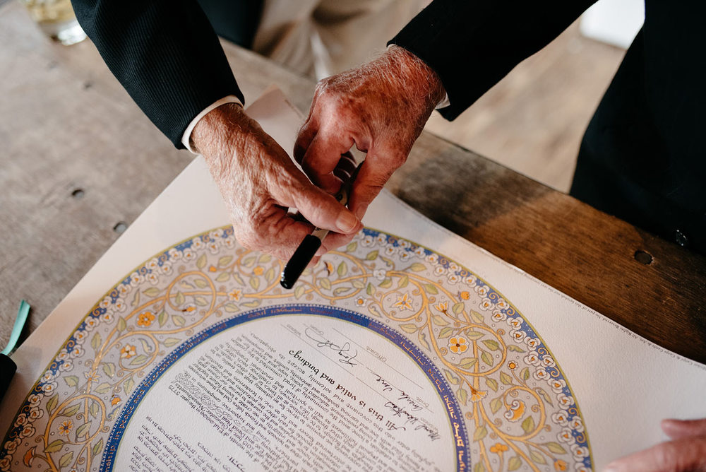 grandparents exchanging pens while signing a ketubah