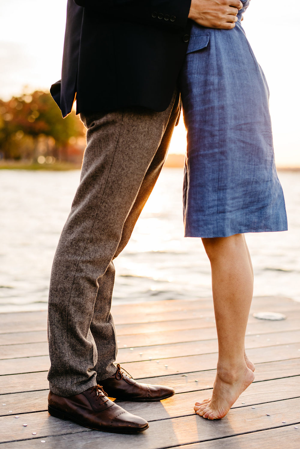 cute couple girl barefoot kissing on the dock at boston esplanade engagement photography