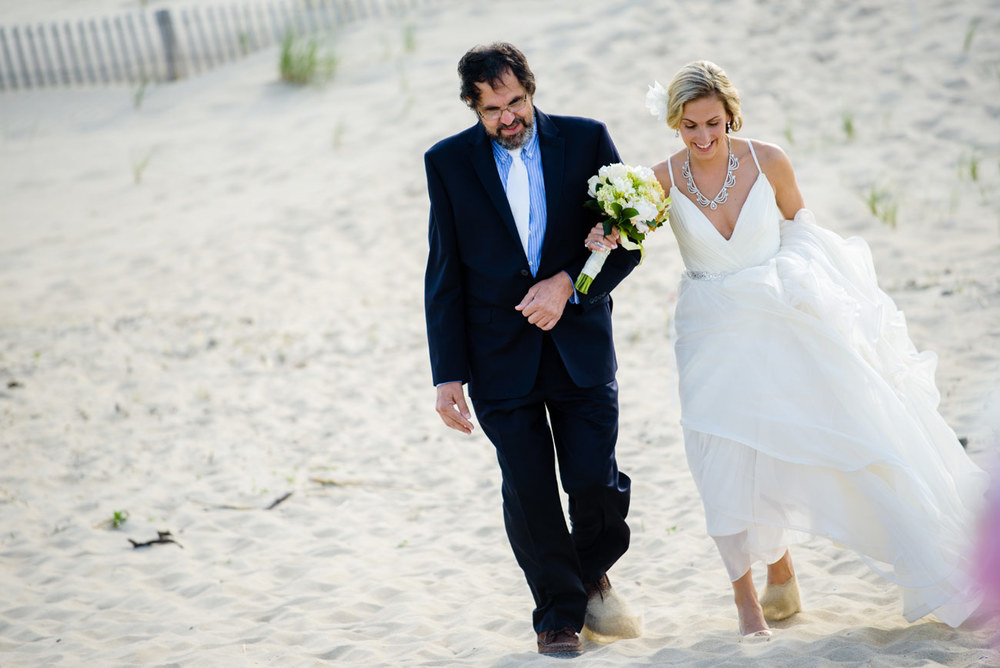 father of the bride walking with the bride on the beach
