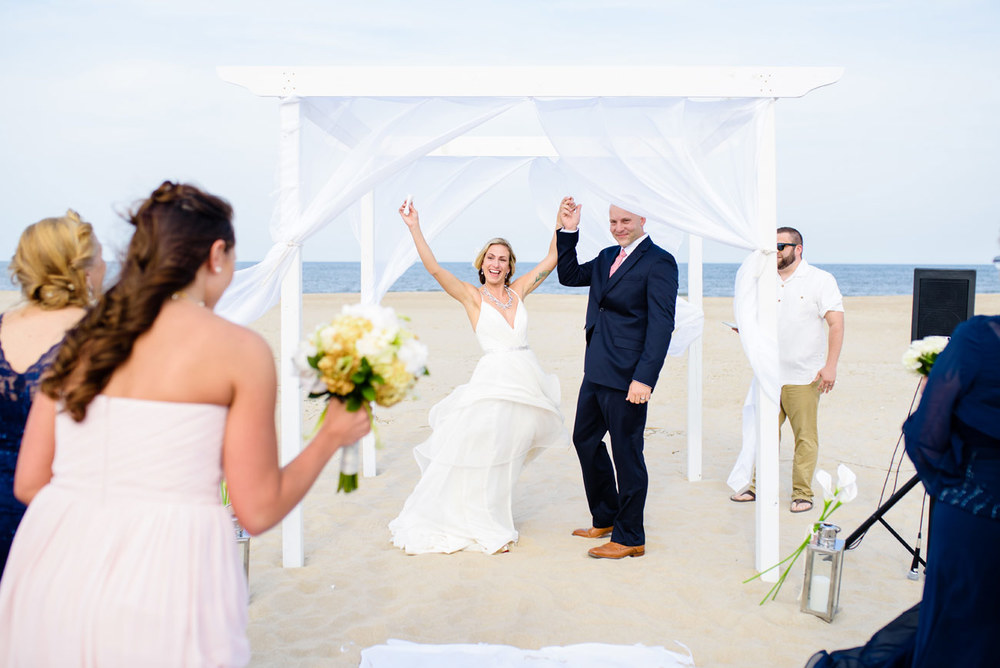 bride and groom after their first kiss celebrating at their destination beach wedding new england cape