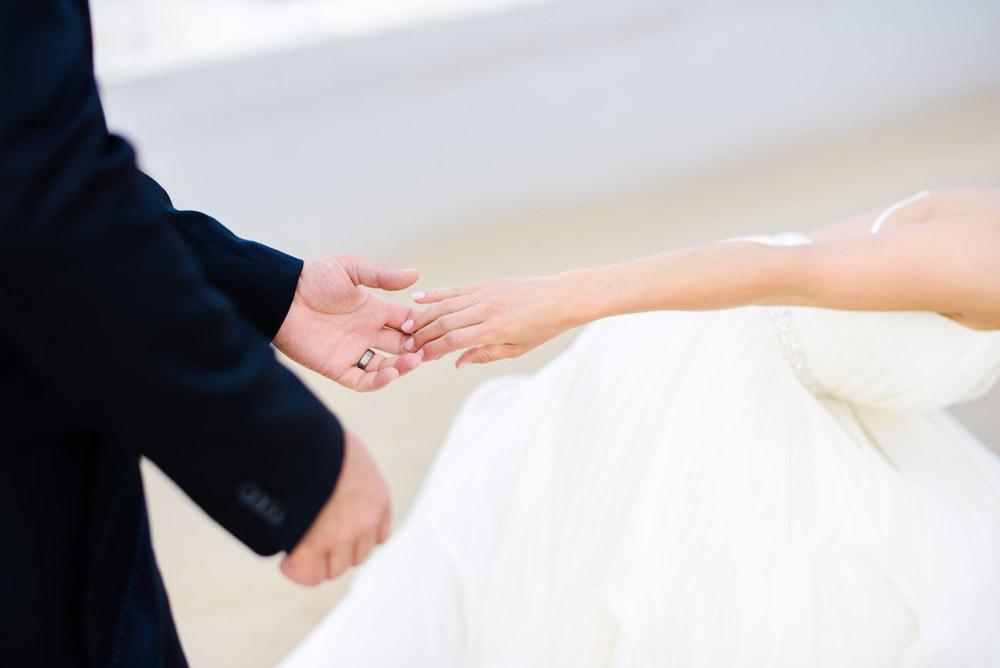 groom holding brides hand on the beach bethany beach and new england weddings