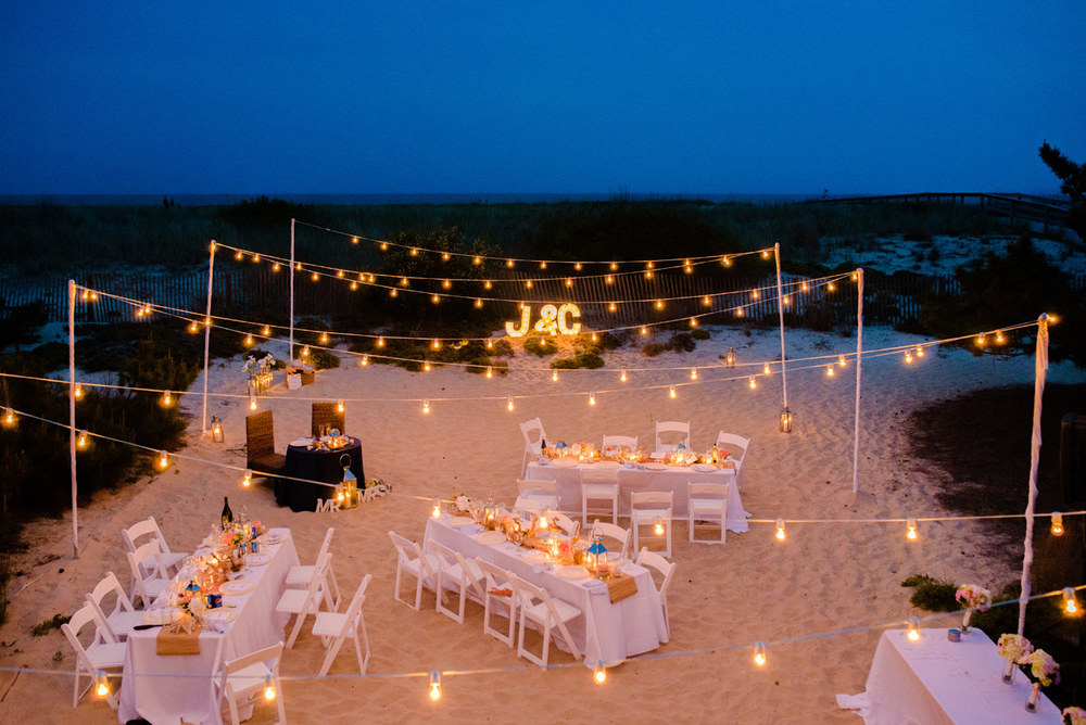 beautifully private estate beach wedding reception at night with cafe lights and details