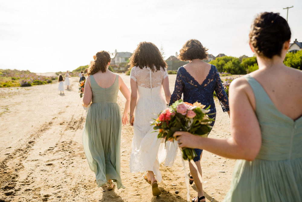 bride and bridesmaids walking to the ceremony on the beach in carlsbad, CA