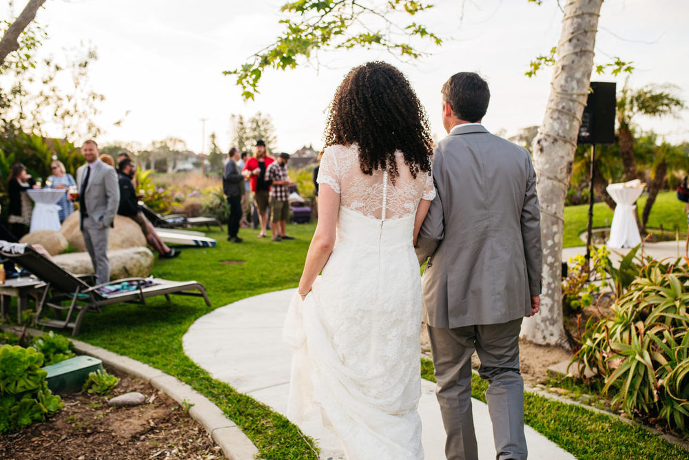 couple walking in to their backyard southern california beach wedding