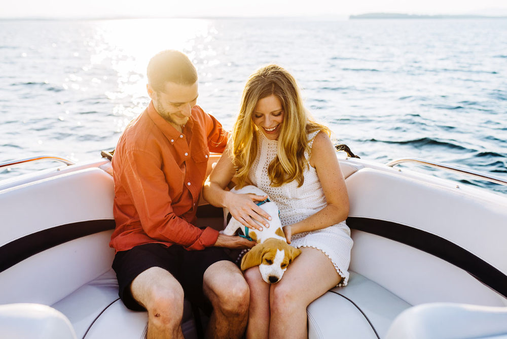 cute couple on a boat on Lake winnipesaukee with their puppy engagement