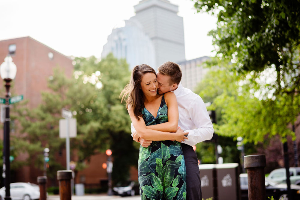 happy engagement photography in boston with views of the prudential building