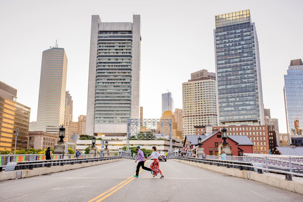 engagement session couple running across congress st. bridge in fort point boston