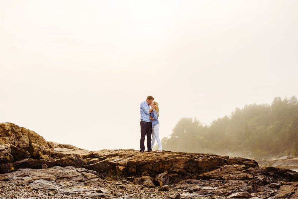 lifestyle new england photography engaged couple on a rock in essex, massachusetts in the fog