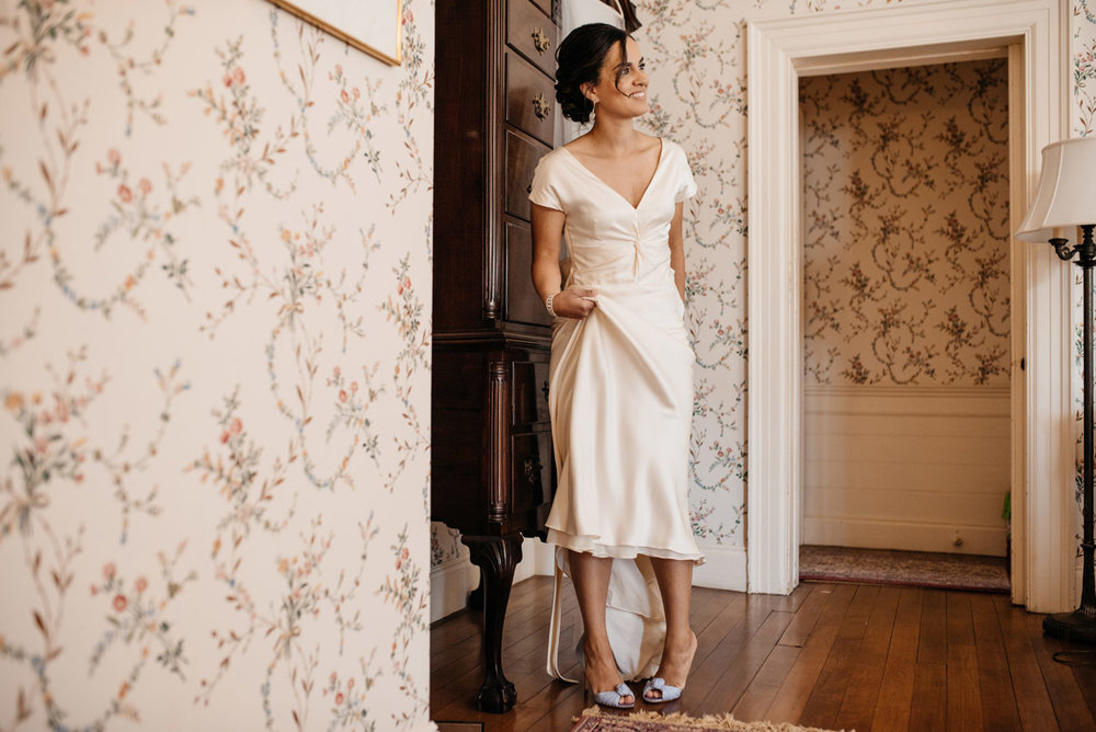 bride putting on shoes at the lyman estate while getting read