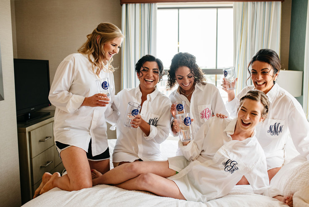 bride with bridesmaids in robes toasting at hotel room