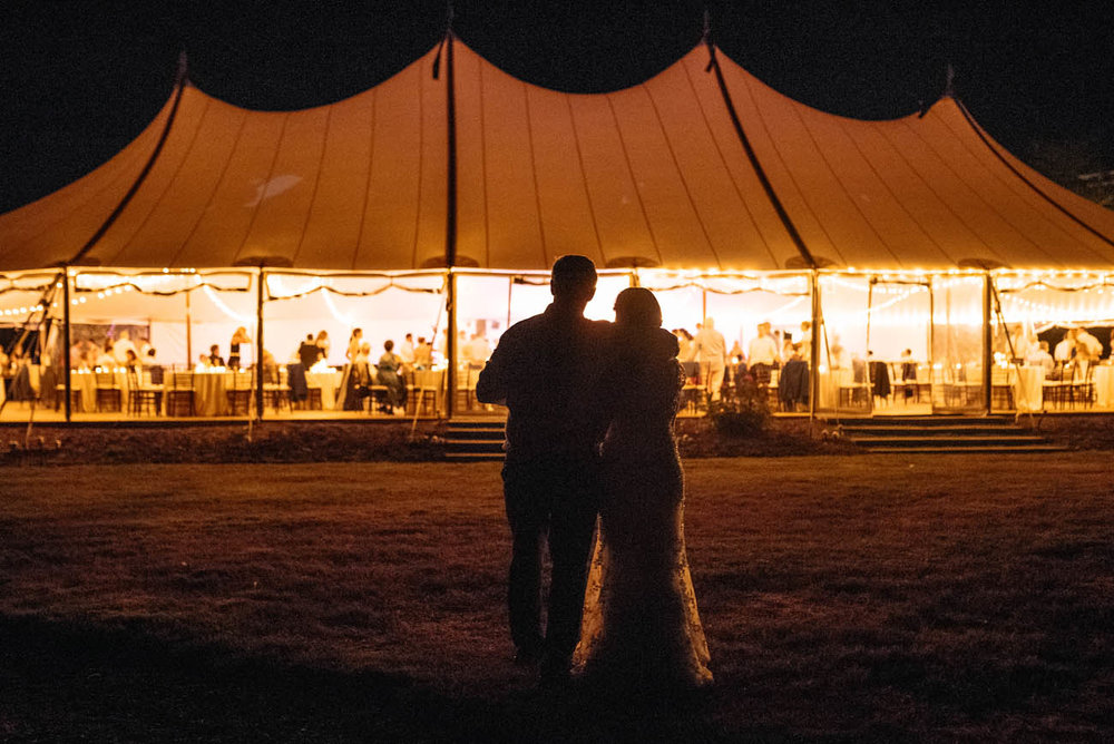 bride and groom looking at tent at night