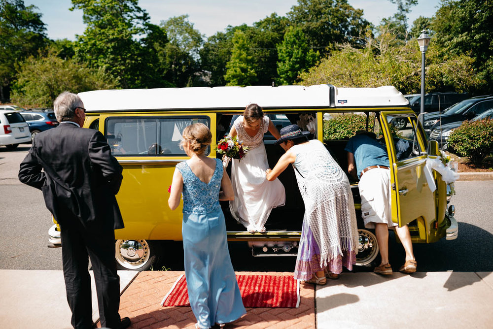 bride getting out of the VW bus at her wedding