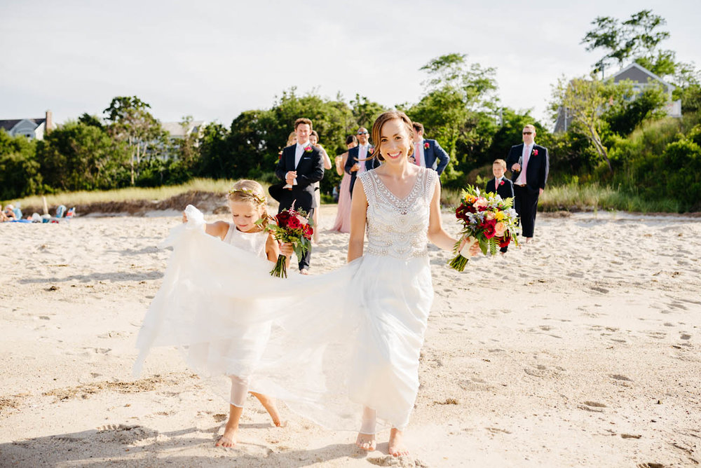adorable flower girl holding brides dress up on the beach