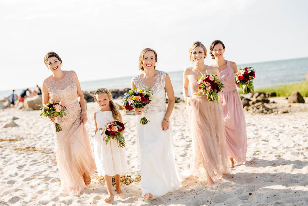 bride and bridesmaids walking on the beach in cape cod