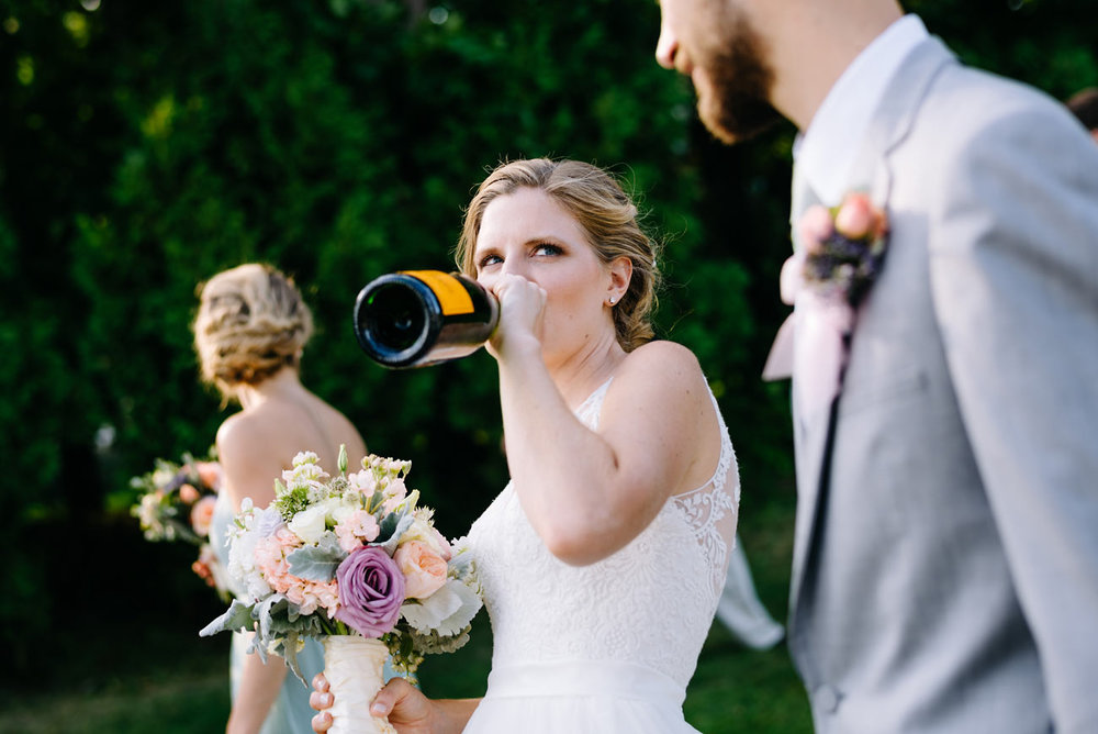 bride chugging champagne at her wediding