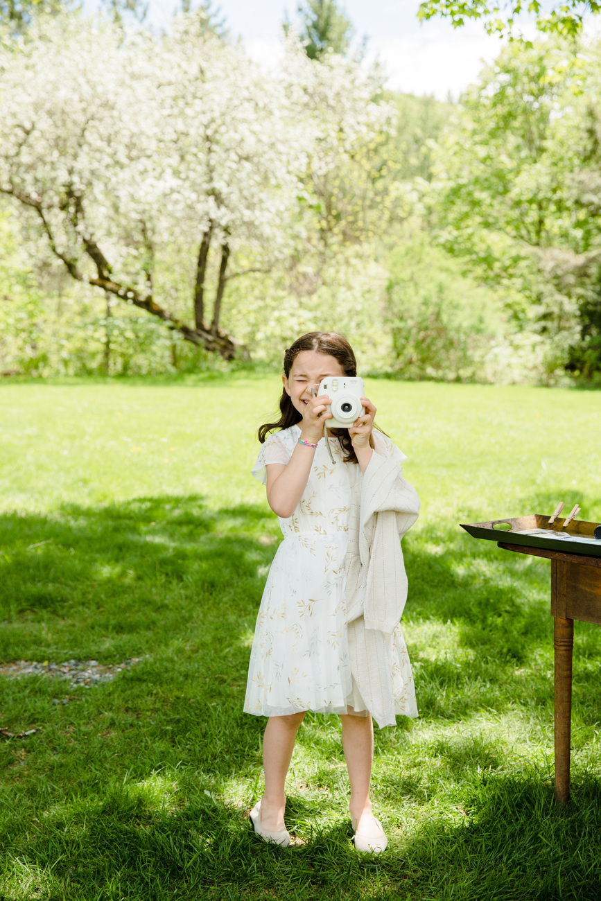 cute kid holding a polaroid camera at a wedding in vermont