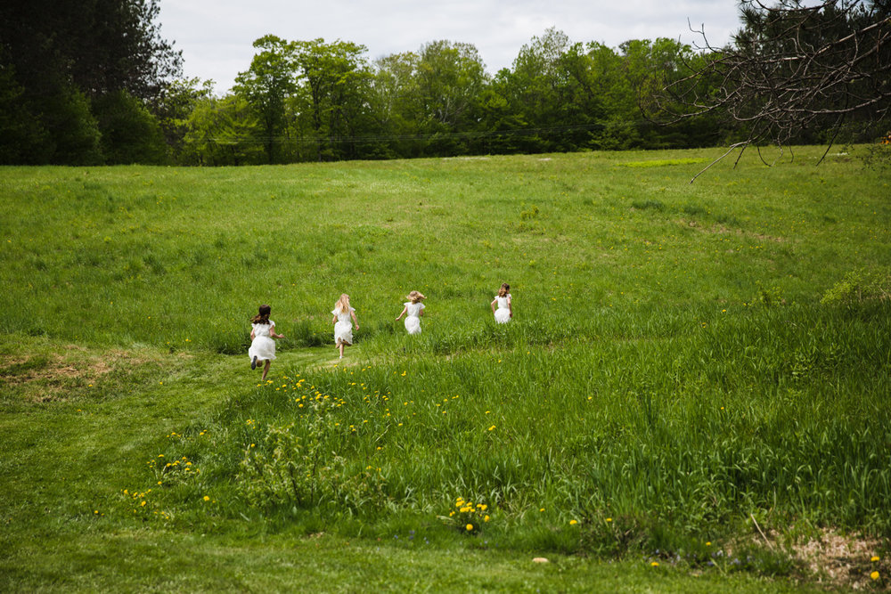 cute flower girls running up a hill in vermont