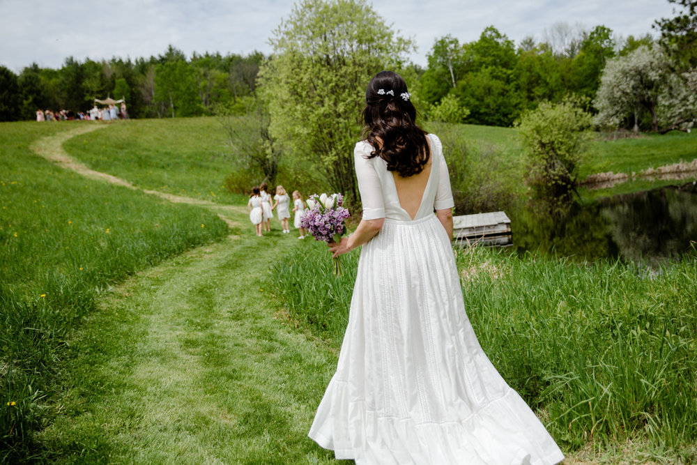 beautiful bride walking to her ceremony on a hill in vermont