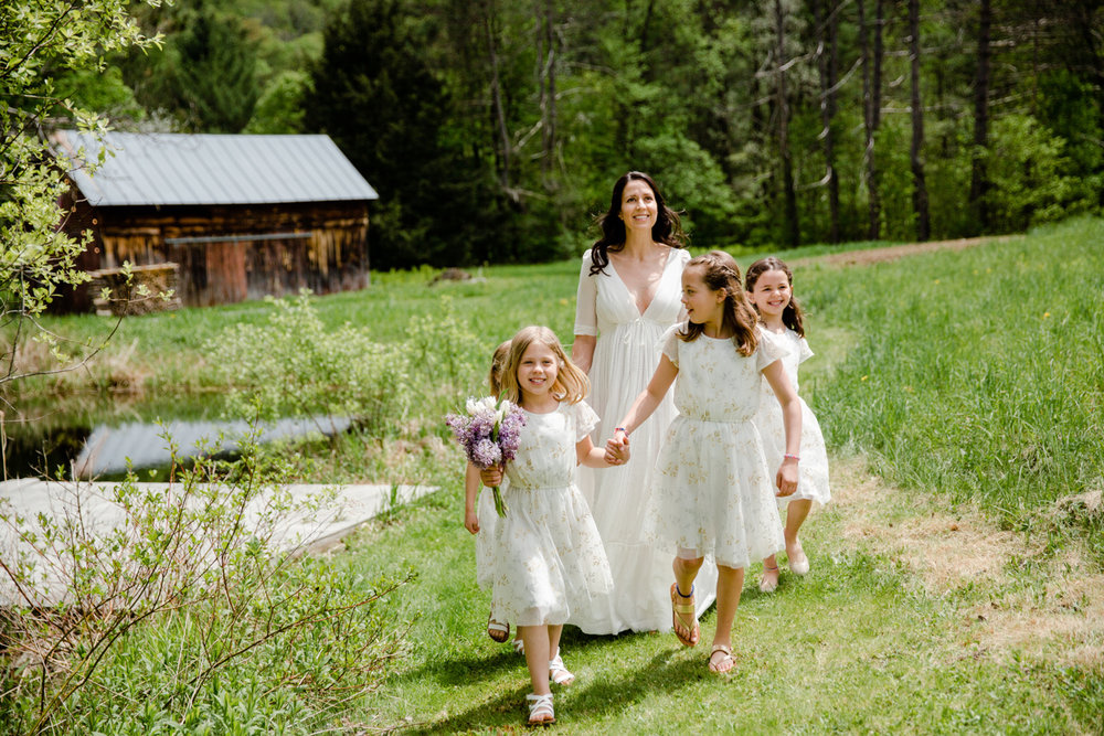 lovely bride with flower girls walking to the ceremony in vermont