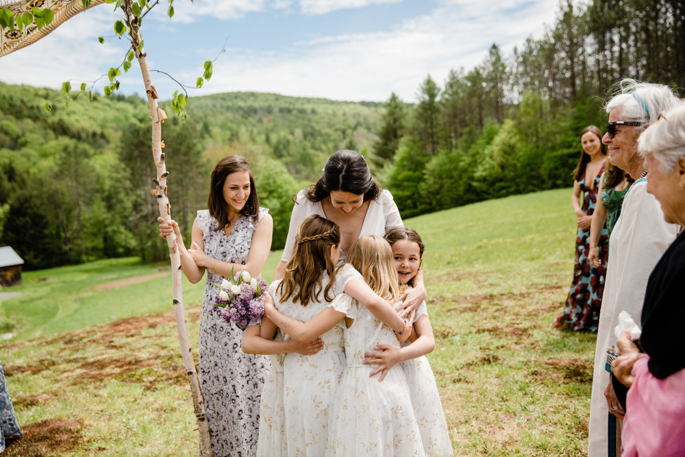 bride hugging flower girls in new england
