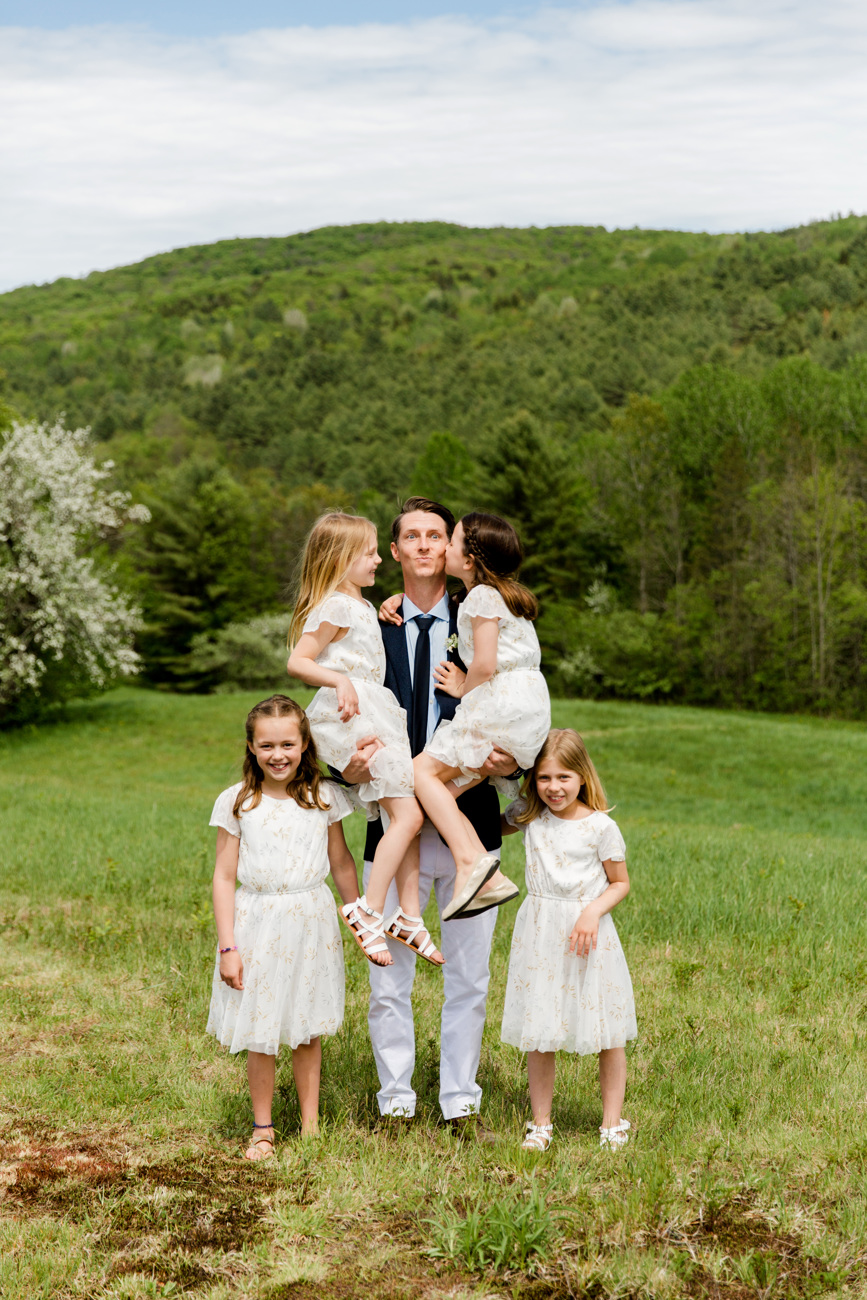 silly flower girls posing with the groom in vermont