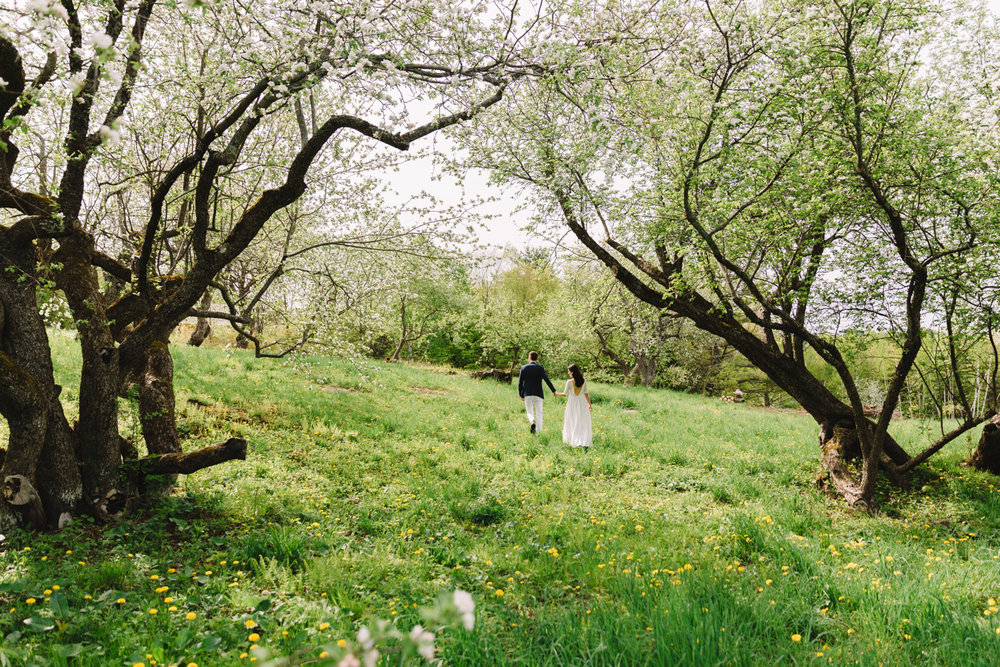 bride and groom walking through the trees in vermont