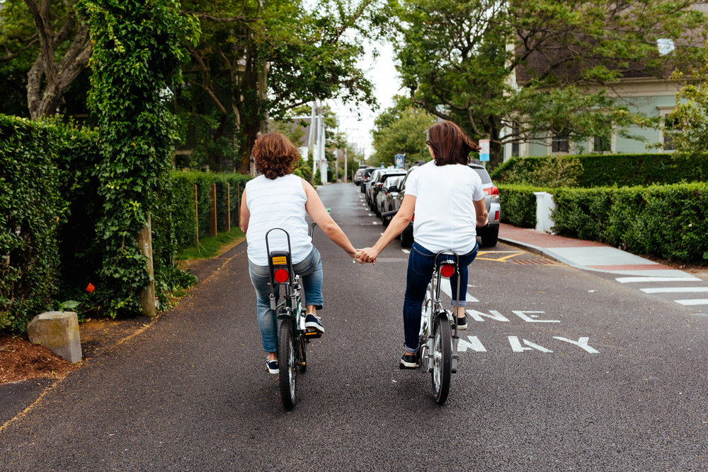 provincetown couple holding hands riding bikes at their elopement
