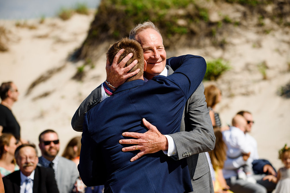 groom and dad candid moment at the beach ceremony in cape cod on the beach